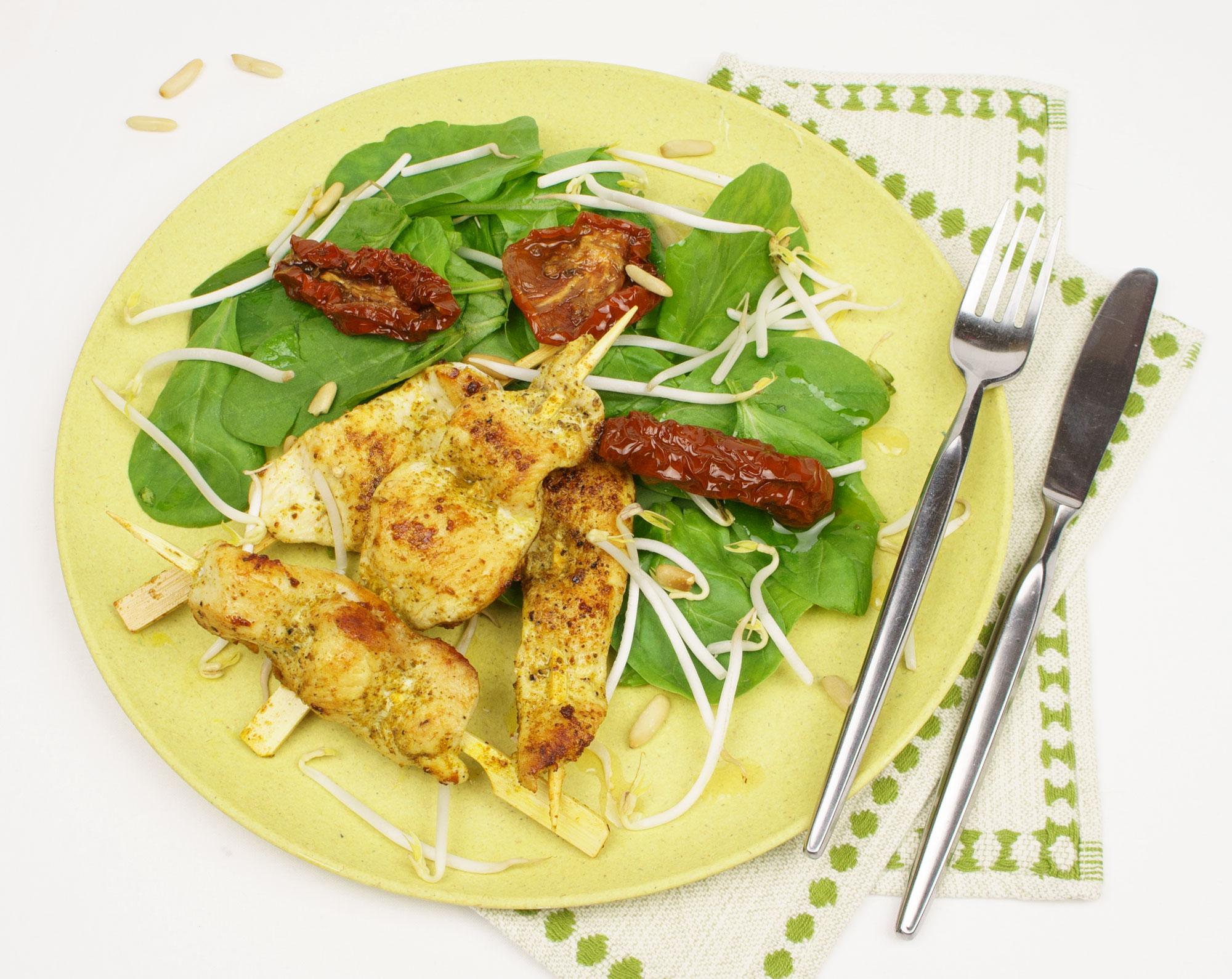 Curry-Hühner Sate Spieße auf Blattspinat mit Sprossen